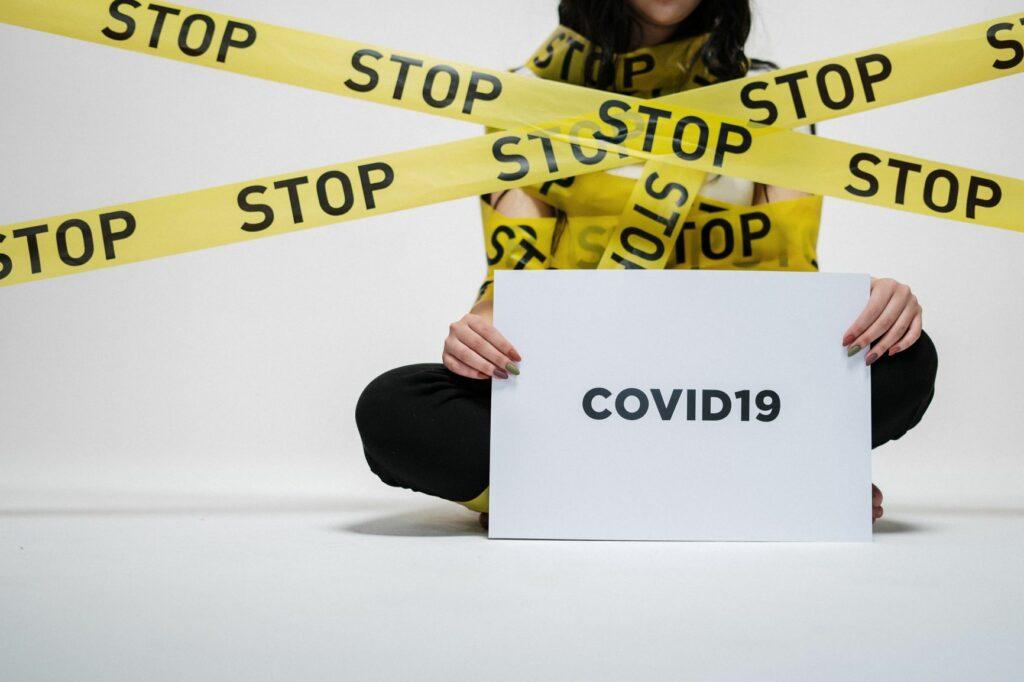 Osoba siedząca na podłodze i trzymająca w dłoniach kartkę z napisem Covid-19.