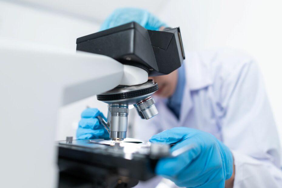 Pracownik laboratorium pochylający się nad mikroskopem i obserwujący materiał badawczy.