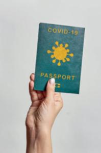 Trzymana w dłoni mała książeczka podpisana Covid-19 Passport.